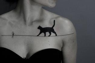 tatuaggi-femminili-gatto-nero-cammina-filo-idea-tattoo-petto-donna-reggiseno-nero-mento